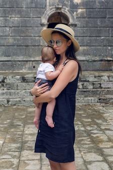 Moeder in de hoed en de zonnebril houdt zijn zoon vast