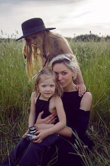 Moeder in een avondjurk en een retro camera met twee dochters op een groen veld met gras in de zomer