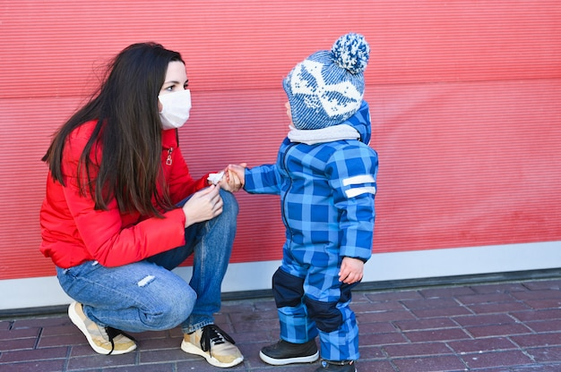 Moeder in een beschermend masker dat met haar kind voor de gek houdt
