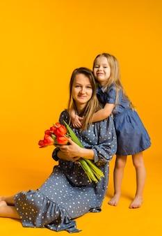 Moeder in een blauwe jurk met een boeket rode tulpen zit met haar dochter op een gele muur