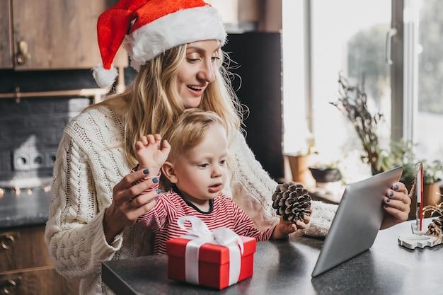 Moeder in een feestelijke nieuwjaarsmuts met zoon aan tafel in de keuken en videogesprekken voeren.