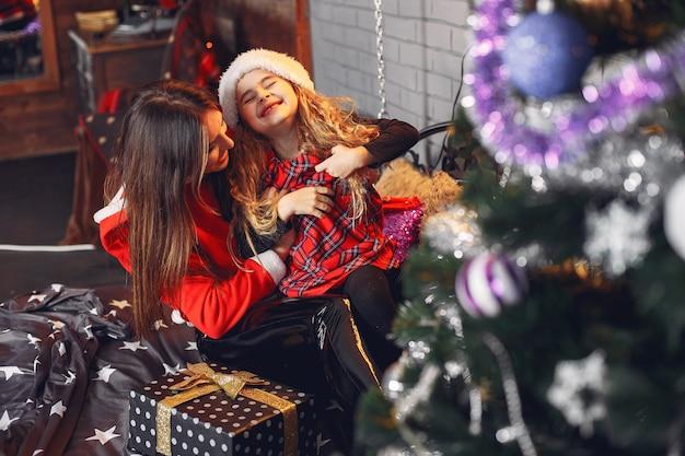 Moeder in een santa's pak met schattige dochter thuis
