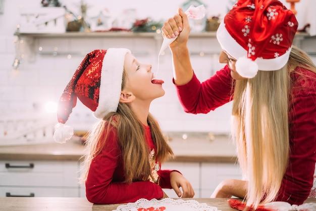Moeder in een schort en haar tienerdochter vermaken zich in de keuken met kerstmutsen