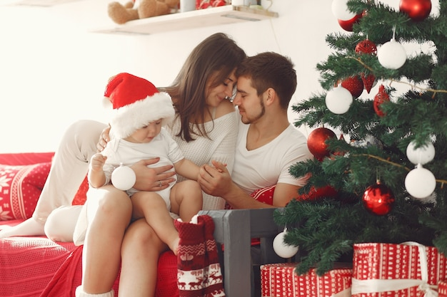 Moeder in een witte trui. familie met kerstcadeaus. kind met ouders in kerstversiering.