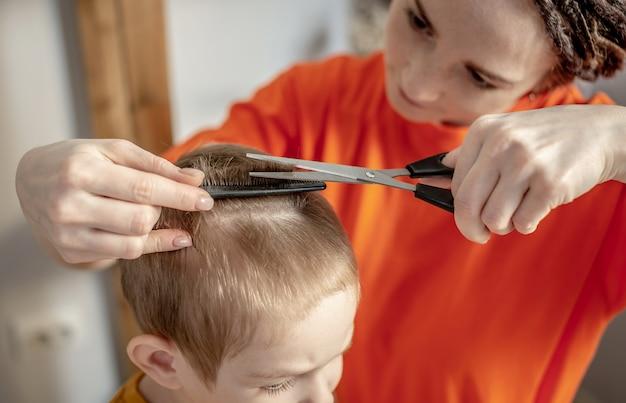 Moeder in lichte kleding knipt het haar van haar zoontjes thuis met een schaar
