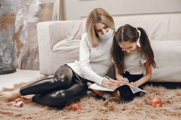 Moeder in masker met dochter op de vloer. meisjeskleuring en moeder die haar helpt.