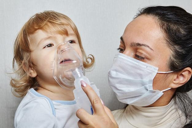 Moeder in medisch masker helpt haar dochtertje met ademen met behulp van een vernevelaar, die luchtwegaandoeningen behandelt.
