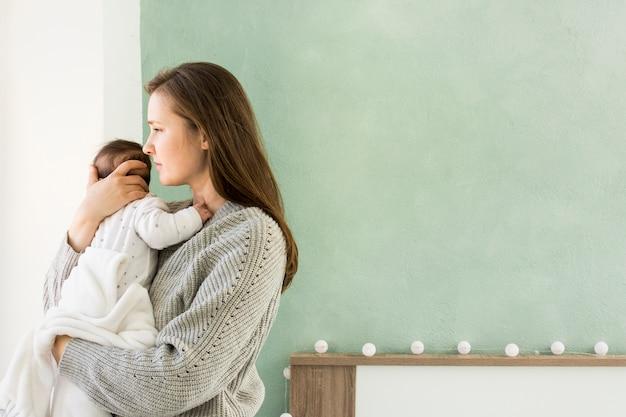 Moeder in sweater die leuke baby koestert