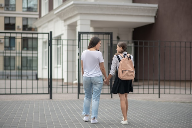 Moeder in t-shirt en spijkerbroek met dochter in schooluniform staan voor school poort glimlachend praten