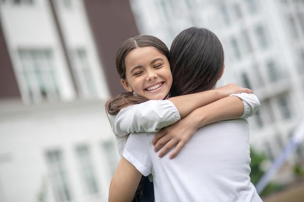 Moeder in witte blouse met haar rug naar de camera gelukkig schoolmeisje dochter knuffelen op schoolplein