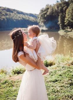 Moeder in witte jurk speelt met haar charmante dochter in witte gawn voor een meer