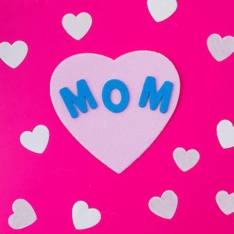 Moeder inscriptie met papieren harten op roze tafel