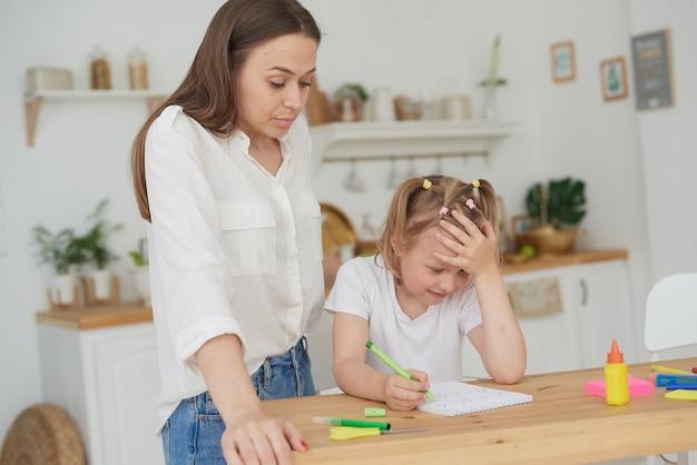 Moeder is boos omdat haar dochter geen huiswerk wil maken. ouders die kinderen thuis onderwijzen, thuisonderwijs, moeder die haar dochter helpt huiswerk te maken, emotionele stress.