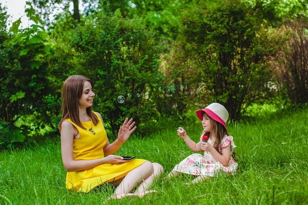 Moeder kijkt als haar dochter blaast zeepbellen