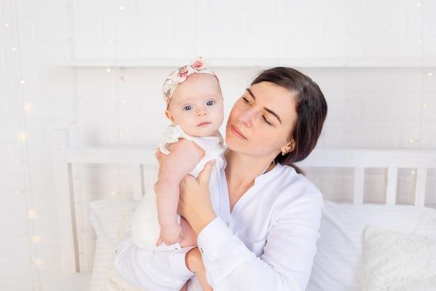 Moeder kijkt angstig naar het meisje op het bed thuis, moederliefde en zorg