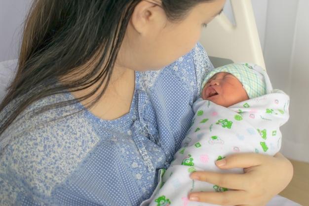 Moeder kijkt naar haar pasgeboren baby in bed onmiddellijk na een bevalling. conceptenfoto van zwangere pasgeboren vrouw, baby, zwangerschap.