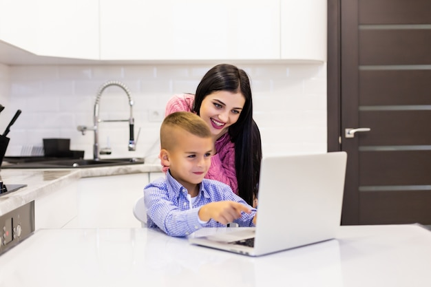 Moeder kijkt over het hoofd terwijl haar zoon zijn laptop gebruikt om in hun keuken te studeren