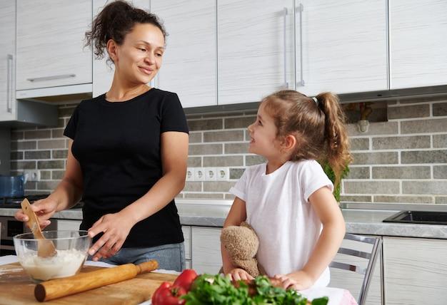 Moeder kijkt schattig naar haar dochtertje en leert hoe ze deeg moet koken voor het bakken van pizza. moeder en dochter bereiden samen deeg.