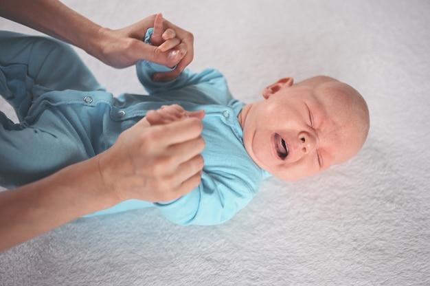 Moeder kleedt schattige emotionele grappige pasgeboren babyjongen in een blauwe jumpsuit baby baby nursery