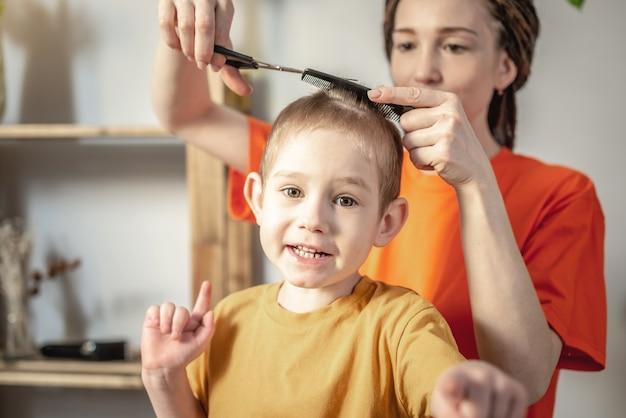 Moeder knipt het haar van het kind thuis met een schaar