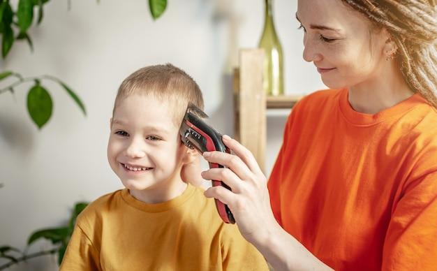 Moeder knipt het haar van het kind thuis met een tondeuse
