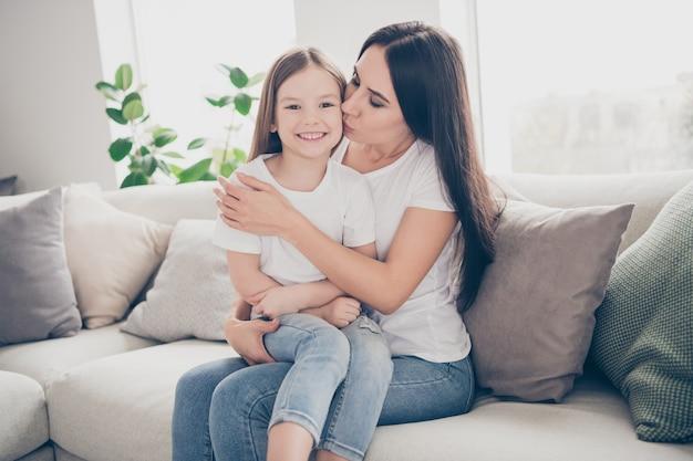 Moeder knuffel en kus haar kleine dochter binnenshuis huis