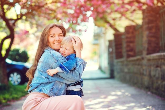 Moeder knuffelen haar trieste zoon. moederschap, gezin en levensstijl. moeder kalmeert haar verdrietig kind buitenshuis.