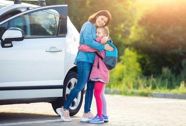 Moeder knuffelen schoolmeisje na lessen over parkeren