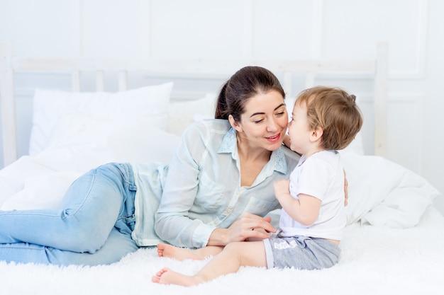 Moeder knuffels baby thuis op het bed het concept van familie en kinderen moederdag