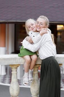 Moeder knuffels dochter in de zomer voor een wandeling in het park