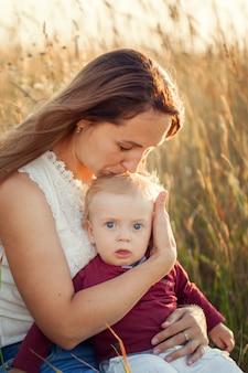 Moeder knuffels en kusjes zijn zoontje in zonnige zomerdag.