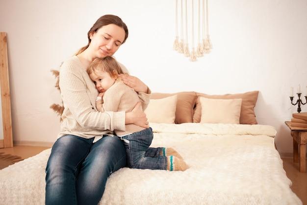 Moeder knuffels houdt van troost het interieur van de baby, een vrouw zit op het bed te beschermen en te verzorgen