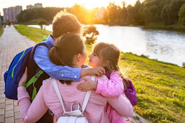Moeder knuffels zoon en dochter stuurt kinderen naar school.