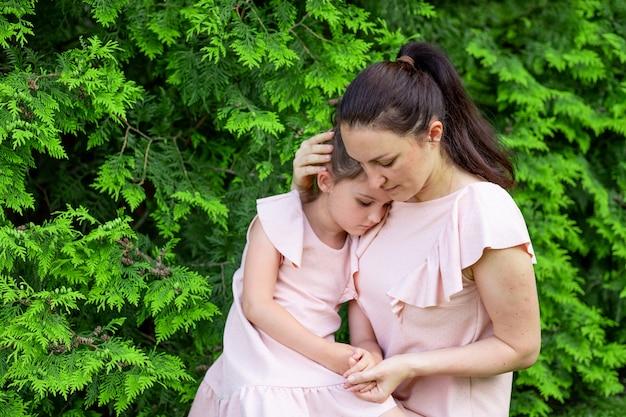Moeder knuffelt dochter 5-6 jaar zittend in het park op het gras, moeder-dochter gesprek, moeder heeft medelijden met het kind, moeder-kind relatie, moederdag