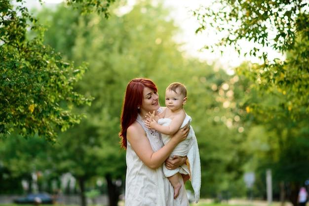 Moeder knuffelt en speelt met haar eenjarige dochter die na het baden in een handdoek gewikkeld is.