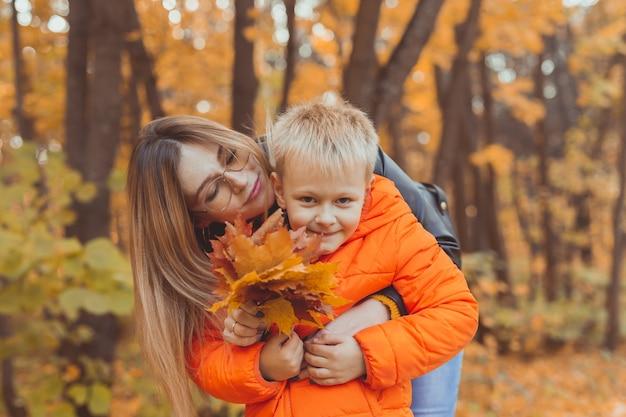 Moeder knuffelt haar kind tijdens wandeling in herfstpark herfstseizoen en alleenstaande ouder concept