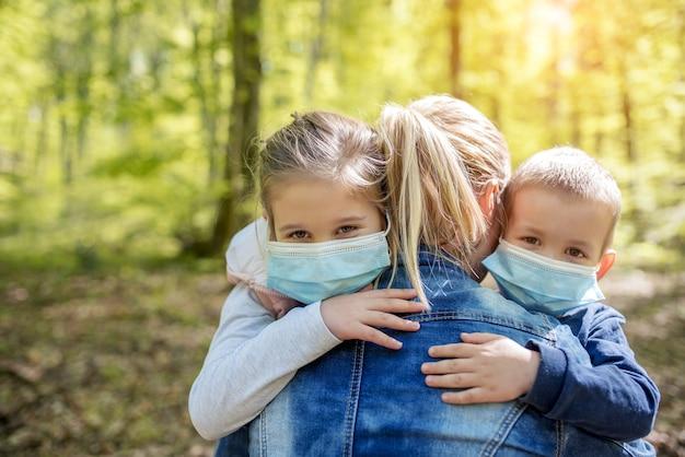 Moeder knuffelt haar kinderen met medische gezichtsmaskers om te worden beschermd tegen het covid-19-virus