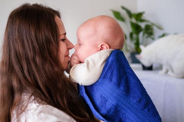 Moeder knuffelt haar kleine schattigste baby na bad met blauwe handdoek op hoofd. zuigelingskind op moederhanden. moederverzorging liefde. gezinsleven. moeder en baby. gelukkig moederschap