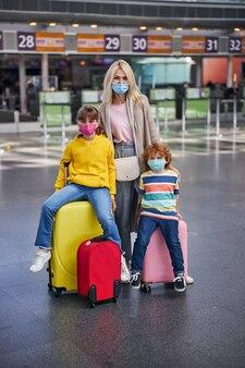 Moeder knuffelt twee kinderen die op koffers zitten