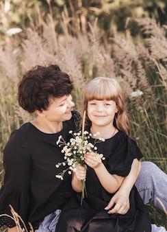 Moeder knuffelt zachtjes haar dochter in de natuur in de zomer, gelukkig moederschap