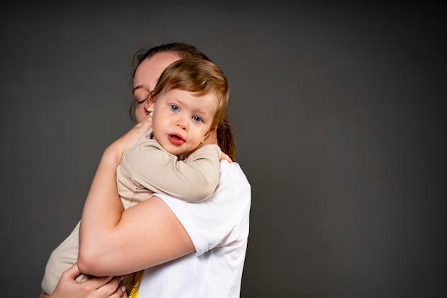 Moeder knuffelt zachtjes haar kind in de studio klein meisje in de armen van de familie van haar ouders