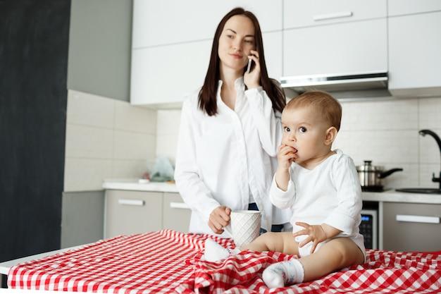 Moeder koffie drinken en praten over de telefoon terwijl baby eten op de keukentafel