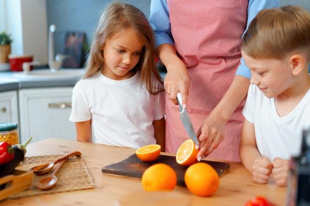 Moeder koken met haar kinderen in de keuken