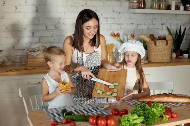 Moeder kookt lunch met de kinderen. een vrouw leert haar dochter koken van haar zoon. vegetarisme en gezond natuurlijk voedsel