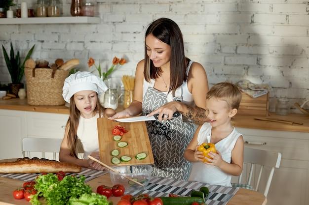 Moeder kookt lunch met de kinderen. een vrouw leert haar dochter koken van haar zoon. vegetarisme en gezonde natuurlijke voeding
