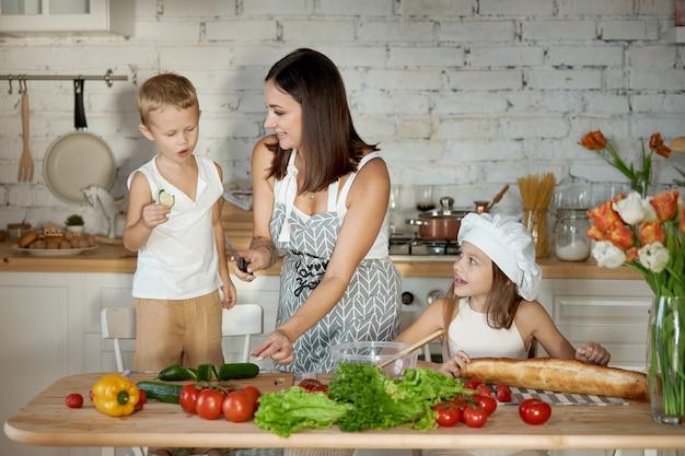 Moeder kookt lunch met de kinderen
