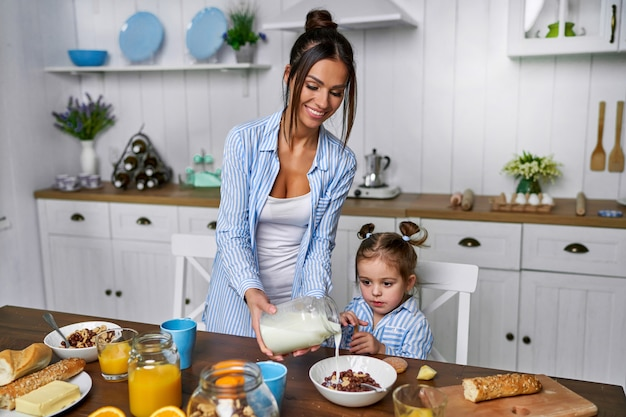 Moeder kookte ontbijt voor haar dochtertje. meisje zal ontbijtgranen eten