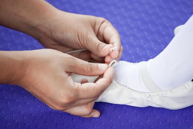 Moeder koppelt voeten pointe schoenen aan haar dochter die voor het praktizeren van een ballet voorbereidingen treft