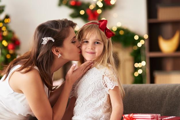 Moeder kussen dochter op wang