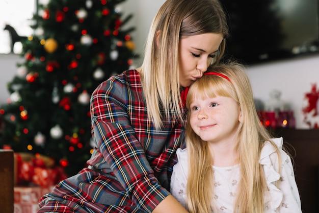 Moeder kussende dochter bij kerstmis
